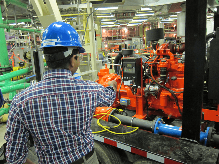 Photo of a CNSC staff member inspecting portable diesel emergency water pumps. These can be used in emergency situations to keep water circulating in the reactor.