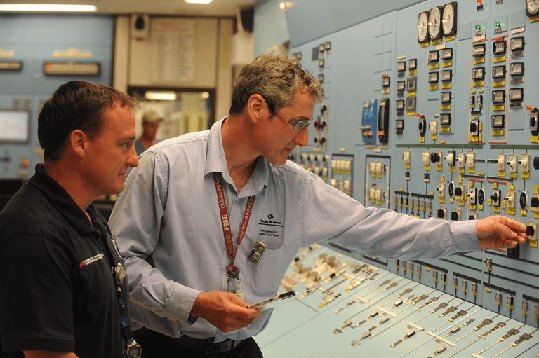 Photo of a control room operator and a CNSC inspector working in the Point Lepreau control room
