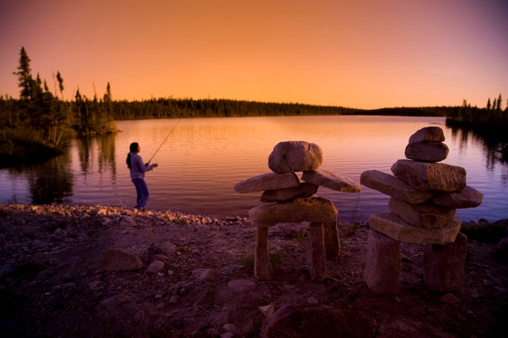 A man fishing in a lake with inukshuks on the shore