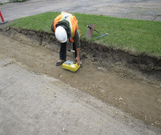 Worker operating a portable gauge to measure soil characteristics