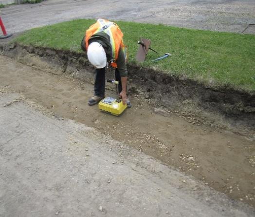 Travailleur utilisant une jauge portative pour mesurer les caractéristiques du sol