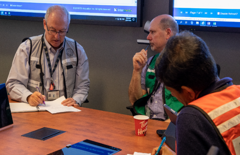 CNSC staff in the Emergency Operations Centre work through the status of the exercise event.