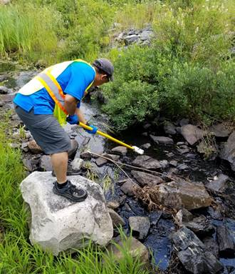 Image    d'un employé de la CCSN prélevant des échantillons d'eau à Elliot Lake