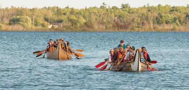Image    de canoës de voyageurs transportant des dirigeants, des dignitaires et le    vice-président de la SGDN chargé de la sélection du site, marquant le début    de l'Assemblée générale annuelle de la Nation métisse de l'Ontario