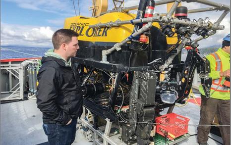 Photo    de Jeff Binns, Ph. D., scientifique spécialiste de la corrosion à la SGDN,    examine le robot utilisé en recherche sous-marine pour étudier les effets de    la pression des eaux profondes sur les matériaux barrière, étude menée en    partenariat avec Ocean Networks Canada de l'Université de Victoria