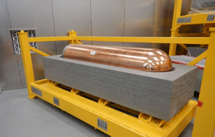 Image of prototype used fuel container in half of highly compacted bentonite clay buffer box