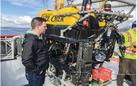 Image of Dr. Jeff Binns, corrosion scientist at the NWMO, examining the robot used in underwater research for the effects of deep water pressure on barrier materials, conducted in partnership with Ocean Networks Canada at the University of Victoria