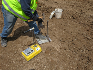Image of a portable gauge being used at a construction site