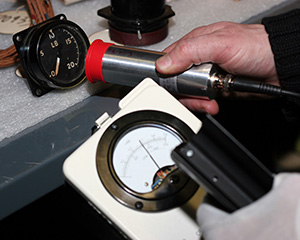 A radiation detection instrument is being used to identify an aircraft instrument that contains radium paint.