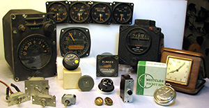 Pictured are a number of devices that contain radium luminous compounds. The devices include vintage military aircraft instruments, toggle switches, vintage consumer timepieces including a pocket watch and a travel alarm clock, instrument knobs, a circuit breaker, and drawer pulls.