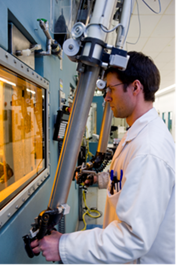 This photo shows a Nordion employee looking into a hot cell and using a manipulator to control robotic arms.